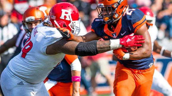 Illinois running back Ra'Von Bonner (21) is tackled by Rutgers defensive lineman Kevin Wilkins (99) during the fourth quarter of an NCAA college football game Saturday, Oct. 14, 2017 at Memorial Stadium in Champaign, Ill. Rutgers defeated Illinois 35-24.