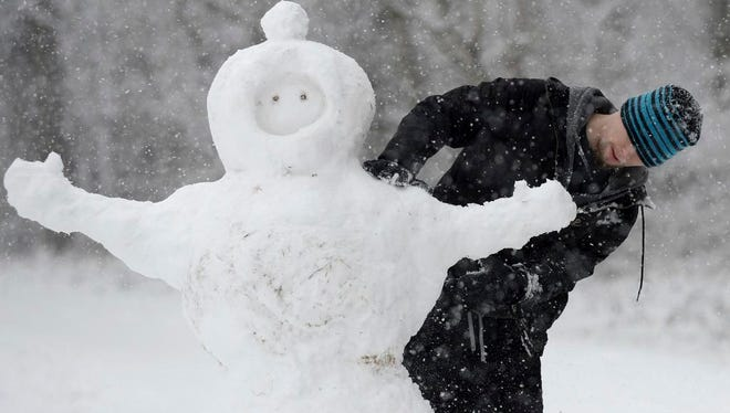"""Aaron Pearce builds a snowman on Wednesday, Jan. 17, 2018, in Charlotte, N.C. A winter storm threatened to dump more than a half-foot of snow Wednesday on parts of North Carolina, canceling school and creating """"nasty"""" road conditions.  (Jeff Siner/The Charlotte Observer via AP)"""