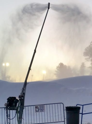 A silhouetted Sheldon Sturtevant oversees snowmaking at the Winter Park snow play area in Ruidoso.