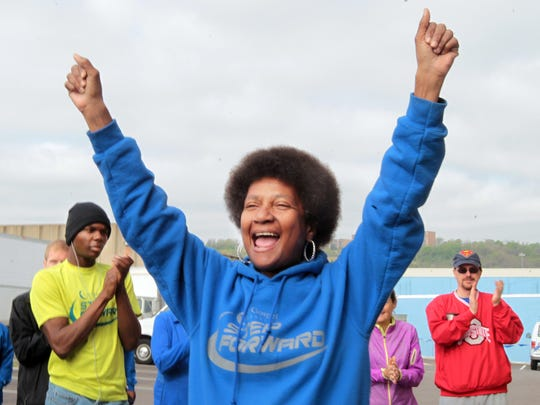 """Belinda Goodgame, a member of the City Gospel Mission's Step Forward running team cheers the announcement of """"Athlete of the Week"""" outside the mission as the team prepares for its final group training run.  A recovering alcoholic and crack cocaine addict, she plans to run the 10K portion of the Flying Pig Marathon."""