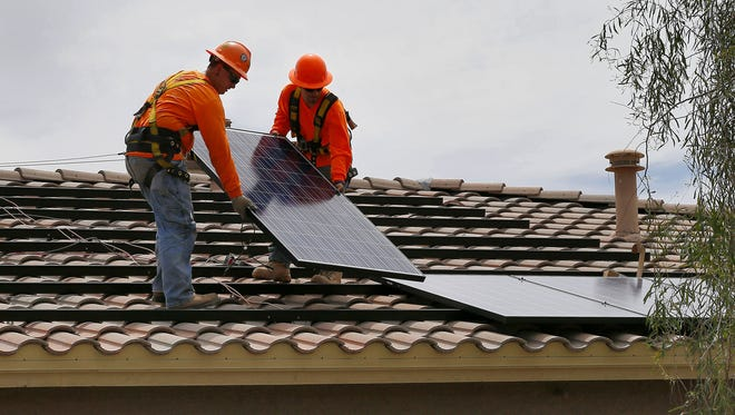 Electricians install solar panels on the roof of a home in Goodyear. Arizona's 7,310 solar-related jobs put it seventh among states last year.