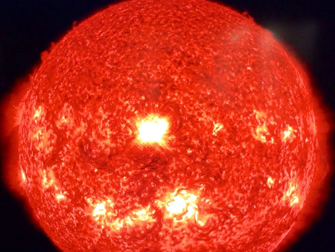 This image of the sun shows the moment a large solar flare, in the center, erupted on Wednesday, spewing forth high-energy particles and plasma.