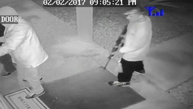 Surveillance video still shows a man stepping forward with what could be an assault rifle as someone inside shuts and locks the door.