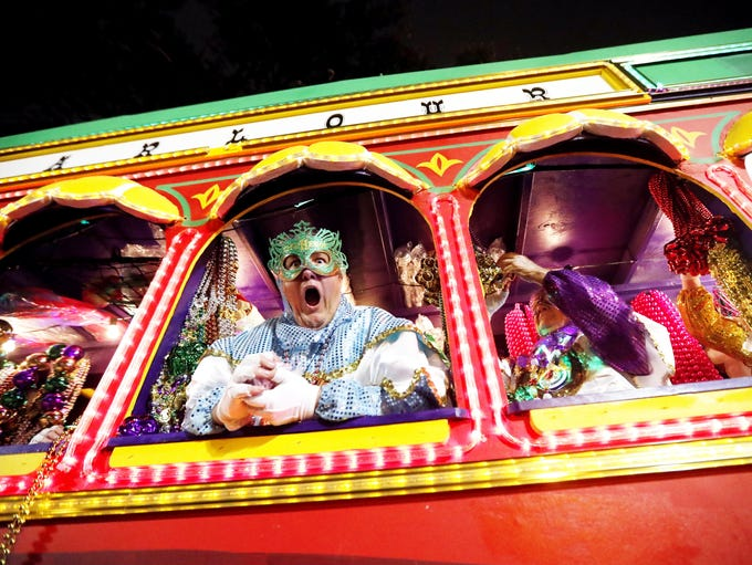 Float riders encourage the crowd as the Krewe of Orpheus
