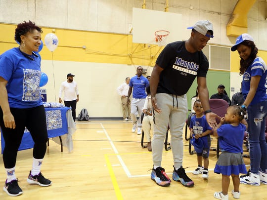 April 11, 2018 - Melony Walker (left), owner of Melony Walker Creative Dizigns, watches as East High School point Alex Lomax greets his siblings, Alexzander Lomax, 3, and Alexcia, 1, before signing his national letter of intent to attend University of Memphis at an event at Lester Community Center on Wednesday.