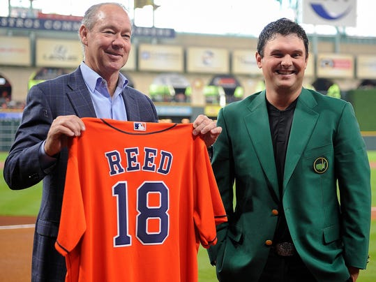 Houston Astros' owner Jim Crane, left, presents 2018 Masters champion Patrick Reed with a Houston Astros jersey before a baseball game against the Texas Rangers, Saturday, April 14, 2018, in Houston. (AP Photo/Eric Christian Smith)
