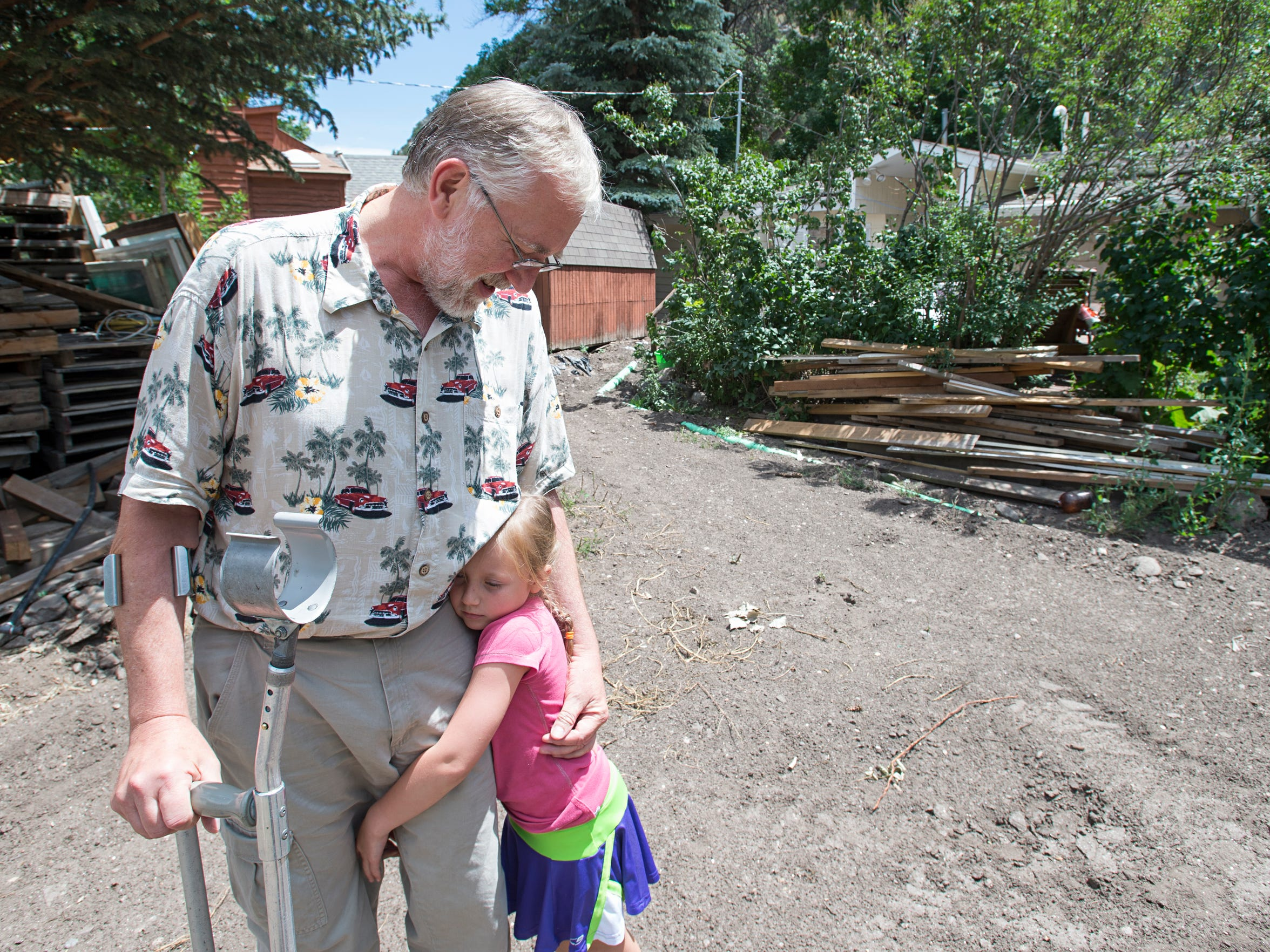 Jerry Shaffer hugs his granddaughter, Audrey, 6, on his property in Drake July 22. Shaffer, a survivor of the 1976 flood of the Big Thompson River, is still working to rebuild his home after another flood moved through the area in 2013.