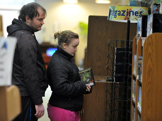 """Brad Uppencamp of Tennyson and """"Alex"""" Minton of Boonville look for movies on DVD and Blu-ray during a visit to the Boonville-Warrick County Library in Boonville. The library is offering several incentives for patrons to check out reading material as part of their summer reading program."""