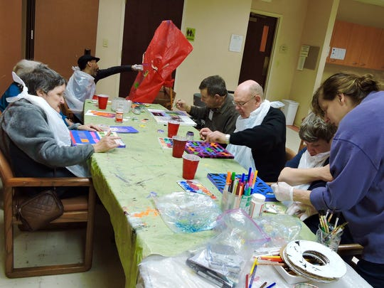 Janice Patrignani, a volunteer from the Visual Art Center of New Jersey in Summit, works with clients at SAGE Eldercare's Spend-A-Day program on art projects geared to enhance memory.