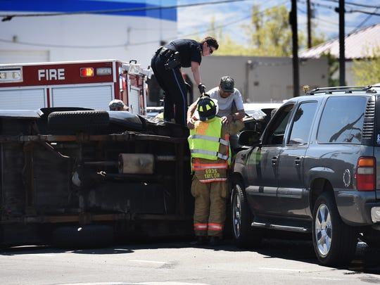 A man is helped out of a rolled over pickup that was involved in a accident on Kuenzli Street and Kirman Avenue this afternoon.