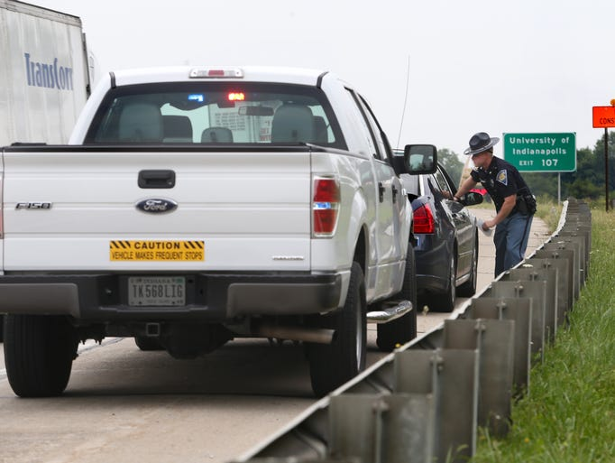 Indiana State Police Trooper Andrew Forgey talks with a driver he caught speeding through a construction zone on I-65 on Indianapolis' Southside on Friday, August 29, 2014. The State Police are using the unmarked INDOT Ford 150 pickup, left, which looks like a construction worker truck, to look for speeders.