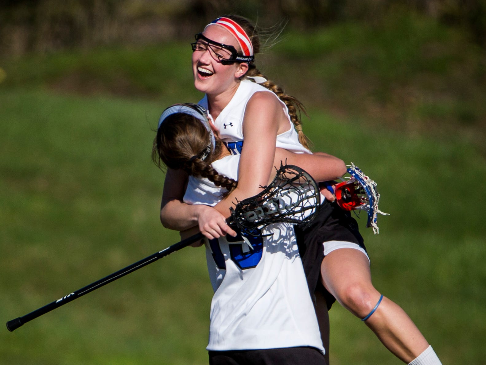 Charter's Kendall Adkins leaps into the arms of teammate Caroline Grasso after defeating Tower Hill 10-9 win at Charter School of Wilmington on Tuesday afternoon.