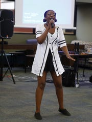 Alena Jenkins, a member of the San Juan College African American Club, sings on Monday during a Martin Luther King Jr. Day celebration at the college in Farmington.