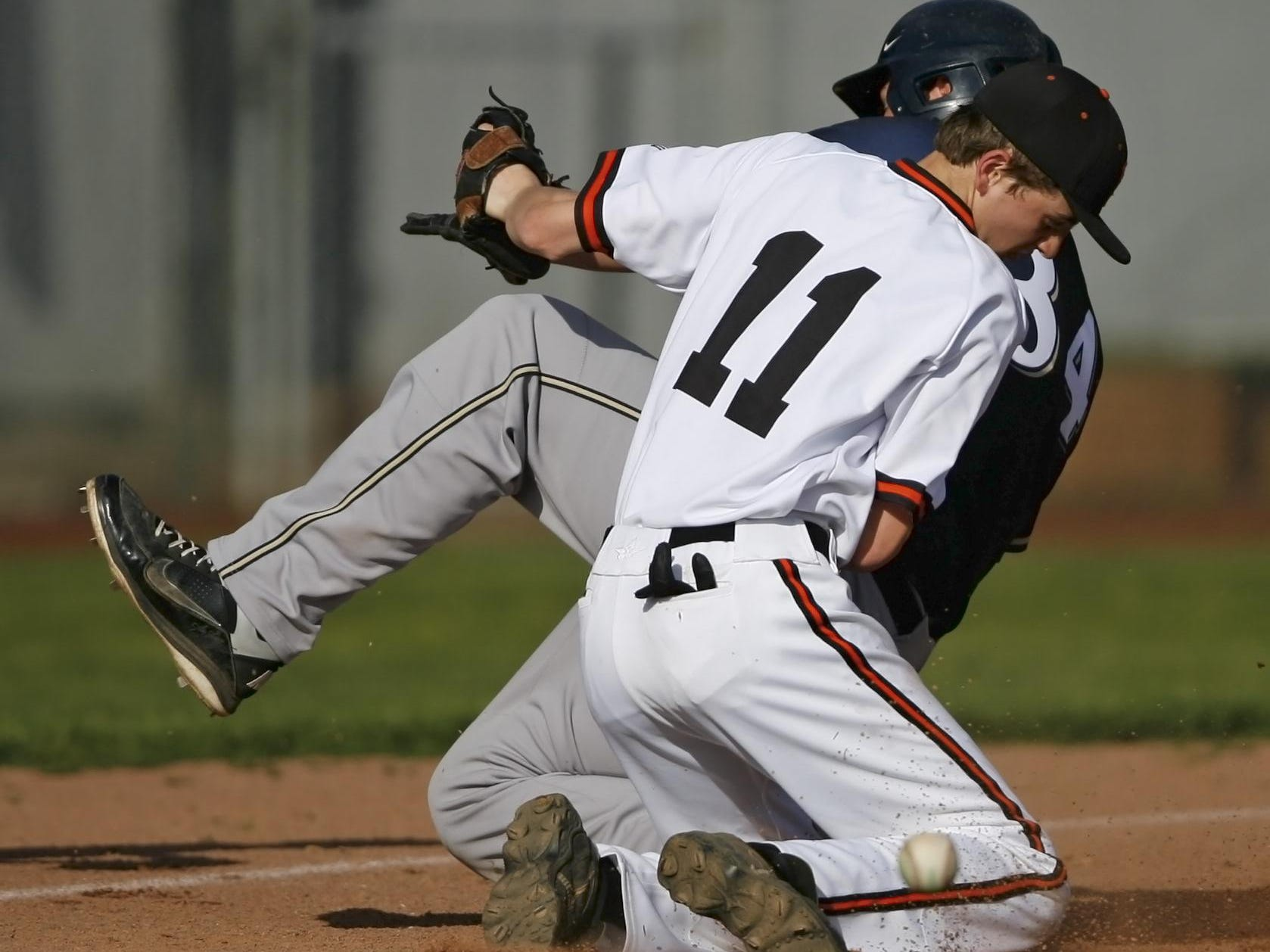 The ball gets away from Silverton third baseman Kirk Martinson as West Albany's Brett Nicholsen slides safely into third during the top of the fifth inning of Silverton's 9-2 loss in a Mid-Willamette Conference baseball game, at Silverton, on Wednesday, Apr. 30, 2914.