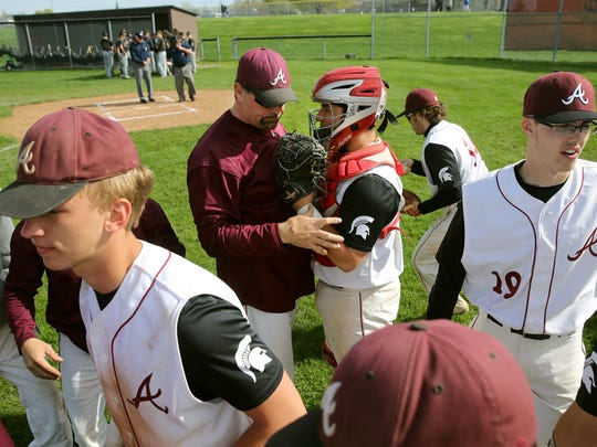 Chris Ruggieri has a word with his catcher as the team breaks a huddle at the start of game against Rush-Henrietta.