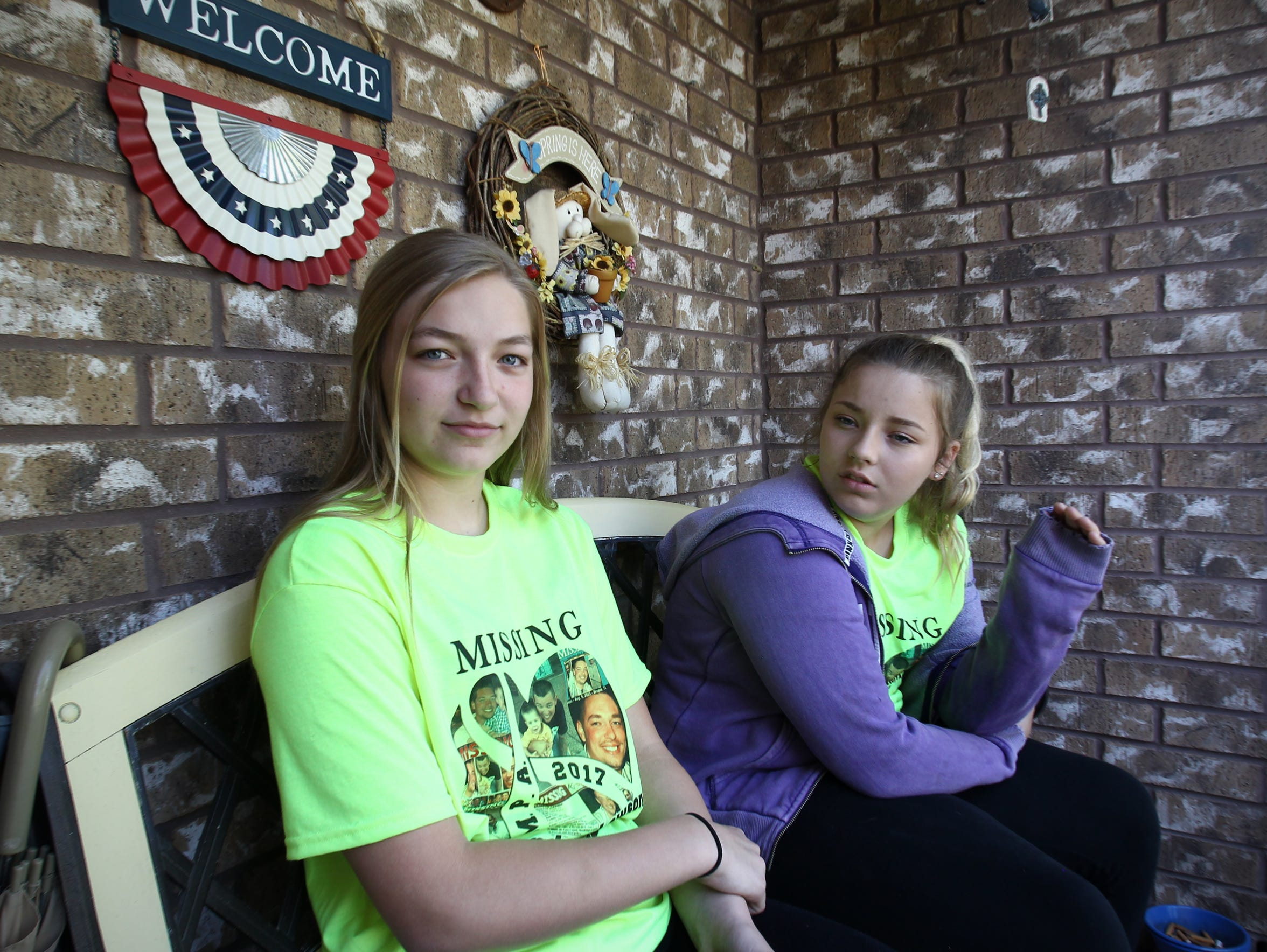 McKenzie Starks, 14, and Destiny Lawson, 11, sit outside