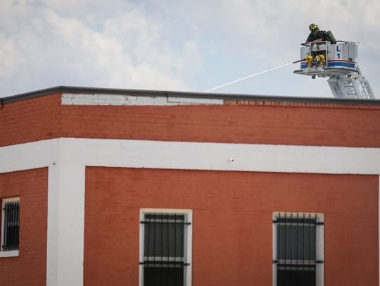 Firefighters on a ladder battle a blaze Saturday, July