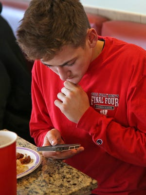 Plainfield High School student Trey Davis reads a screen grab of a violent social media post that lead to closure of his school, Thursday, December 17, 2015.  Instead of school, Davis had lunch with his friends at Panda Express at Plainfield Commons.