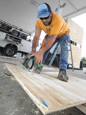 Oliver Sandoval with Dystra Construction cut sheets of plywood last week to cover the gas pump to protect them during the building of a new Circle K convenience store at 17th Street and Pine Avenue in Ocala. Marion County unemployment dipped to 8.5% in June.