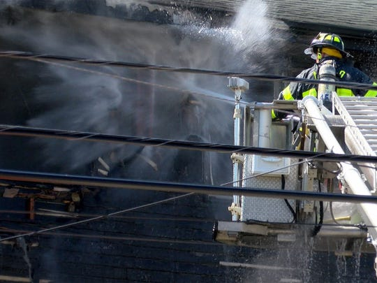 Firefighters work to contain a fire in a Park Avenue condo complex in Asbury Park Monday afternoon, July 9, 2018.