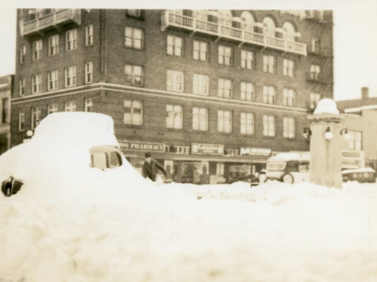 A man shovels out a car on State Street after the big snow of 1937. Franklin Building/Masonic Temple can be seen in the background.