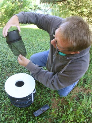 A Shawnee County Health Department employee checks a trap that department maintains to monitor the presence of mosquitoes. [June 2017 file photo/The Capital-Journa[