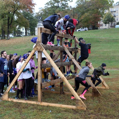 Competitors climb an obstacle as part of the event