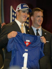 Eli Manning, quarterback from Mississippi, holding up a Giants jersey while standing next to his brother Peyton, at the 2004 NFL Draft. Manning was the number one draft pick in the first round by the Chargers and traded to the Giants.
