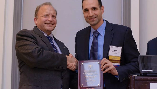 Rep. Dr. John Bizon, left, awarded the Michigan Podiatric Medical Association's Legislator of the Year award by the organization's president, Dr. Ali Safiedine.