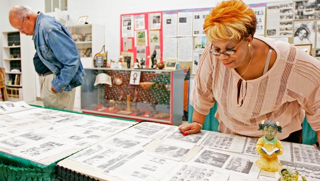 Nita Bellamy looks over yearbook photos from Rosenwald School in Waynesboro in the Waynesboro African-American Heritage Museum that is housed in the former school on Wednesday, Nov. 2, 2016. Bellamy attended Rosenwald, but transferred to Waynesboro High School where she graduated.
