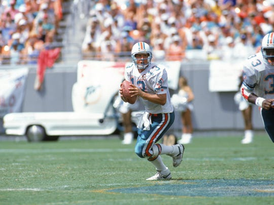 Quarterback Dan Marino of the Miami Dolphins scrambles with the ball as he looks for a receiver.