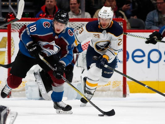Colorado Avalanche right wing Sven Andrighetto, front, of Switzerland, picks up a loose puck in front of Buffalo Sabres right wing Jason Pominville in the first period of an NHL hockey game Tuesday, Dec. 5, 2017, in Denver. (AP Photo/David Zalubowski)