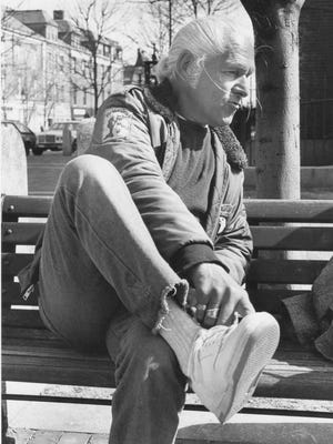 """Dominic """"Ace"""" Karlo shows off his new sneakers in Portsmouth's Market Square prior to raising funds at a charity walkathon in 1986."""