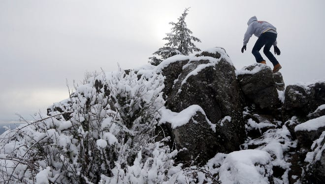Chase Tavernier climbs to the snow-covered summit of Spencer Butte Dec. 7, 2016 in Eugene, Ore. While the snow level dropped low enough to dump snow on the upper reaches of 2,058 feet tall Spencer Butte early in the week, snow is expected to fall in the valley.