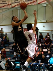 Navajo Prep's Isaiah Chavez takes a shot while defended