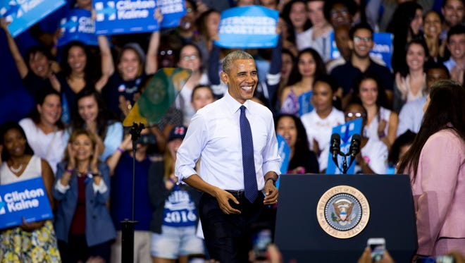 President Barack Obama makes his entrance onto the stage after being introduced by Gabby Pacheco Santos, right, while campaigning for Democratic presidential nominee Hillary Clinton at Florida International University Thursday, November 3, 2016 in Miami.
