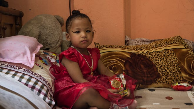 Nepal's newly appointed Living Goddess Kumari Trishna Shakya, 3, looks on in her private home before she is formally taken to the Kumari house in Kathmandu, Nepal, on Sept. 28, 2017.