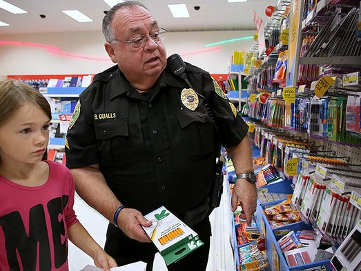 MPD Sgt. Bruce Qualls picks out pencils with Makenzy Bedwell, 8. Heroes and Helpers, formerly Shop with a Cop, held a back to school shopping spree at Target Saturday morning.