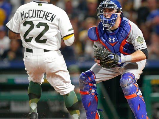 New York Mets catcher Travis d'Arnaud, right, smiles while waiting to tag Pittsburgh Pirates' Andrew McCutchen (22) who was trying to score from second base on a ground ball by Francisco Cervelli in the sixth inning of a baseball game, Saturday, May 27, 2017, in Pittsburgh. (AP Photo/Keith Srakocic)