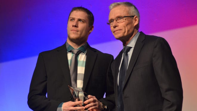 St. Cloud State's Ethan Prow (left) receives one of his three NCHC awards from Western Michigan coach Andy Murray on Thursday at the Muse Event Center in Minneapolis. Prow was named the NCHC's Player of the Year, Defenseman of the Year and Offensive Defenseman of the Year.
