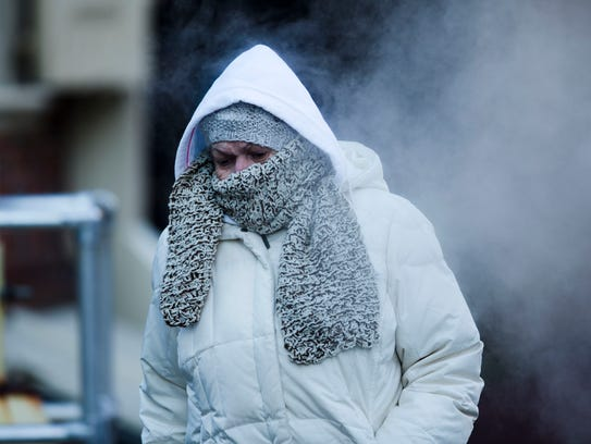 A commuter walks along Market Street in freezing temperatures