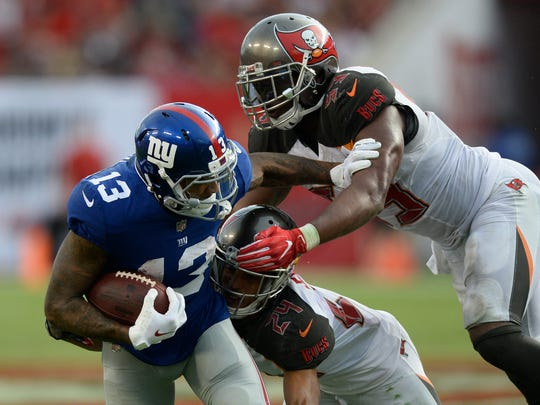 New York Giants wide receiver Odell Beckham (13) is stopped by Tampa Bay Buccaneers cornerback Brent Grimes (24) and outside linebacker Adarius Glanton after a reception during the fourth quarter of an NFL football game Sunday, Oct. 1, 2017, in Tampa, Fla. (AP Photo/Jason Behnken)