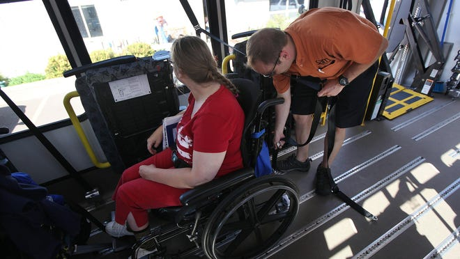 Luca Papini (right), paratransit driver, helps secure Jamie Jo Johnson on the Sioux Area Metro Paratransit bus off of S. Norton Ave. on Sept. 17.