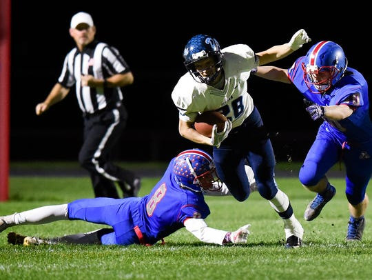 Becker fullback Sidney Boros is brought down by St. Cloud Apollo's Tanner Blommer, 8, and Chris Hance (right) last season at Apollo. Hance should be one of the top linebackers in the area this season.