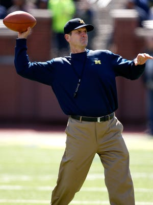 Michigan football coach Jim Harbaugh throws during the spring game April 4, 2015, at Michigan Stadium in Ann Arbor.