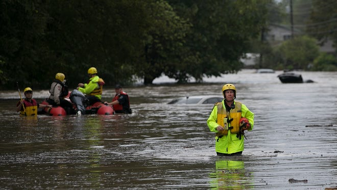 Rescue personnel go out in search of people trapped by a rising Onion Creek on Bluff Springs Road, Friday, Oct. 30, 2015 in Austin, Texas. A fast-moving storm packing heavy rain and destructive winds overwhelmed rivers and prompted evacuations Friday in the same area of Central Texas that saw devastating spring floods.