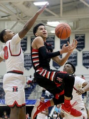 Hughes' Giovanni Santiago drives to the basket  during