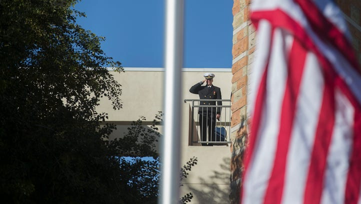 A navy service member salutes as a flag is raised at