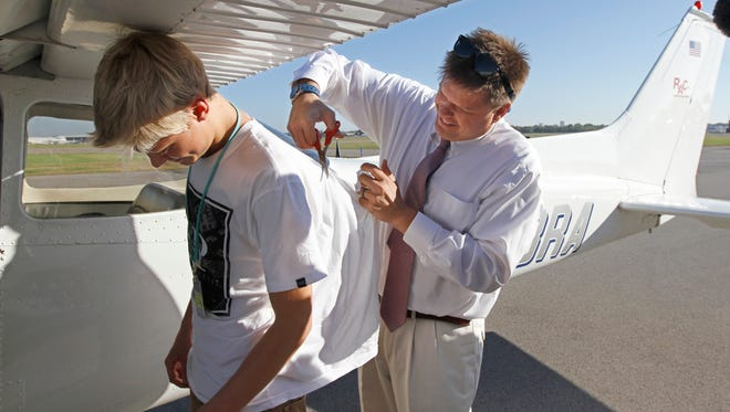 Proud father Chris Schubert, Canandaigua, does the tradition of cutting Matthew Schubert's shirt after his first solo flight from the Rochester Air Center on Scottsville Road in Rochester Friday, Sept. 26, 2014.  The tradition symbolizes a pilot getting their wings.