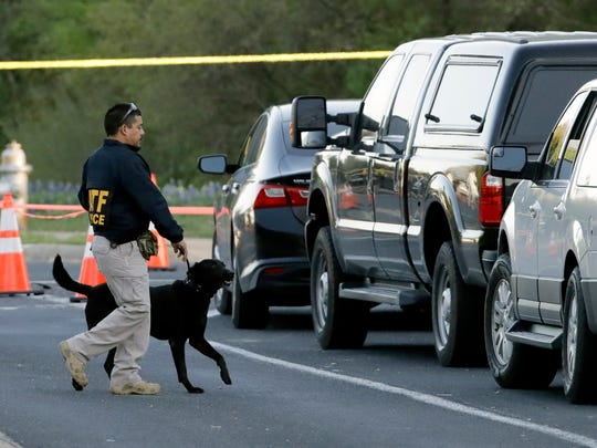 """An agent the Bureau of Alcohol, Tobacco, Firearms and Explosives works with his dog near the site of Sunday's explosion on March 19, 2018 in Austin, Texas. Fear escalated across Austin on Monday after the fourth bombing this month Ñ this time, a blast that was triggered by a tripwire and demonstrated what police said was a """"higher level of sophistication"""" than the package bombs used in the previous attacks."""